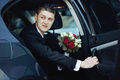 Handsome emotional groom with roses bouquet getting out luxury c Royalty Free Stock Photo