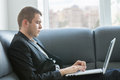 Handsome executive typing at laptop seriously close up his the relaxing couch area Stock Photography