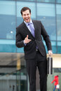 Handsome and expresive businessman in front of an office building with a briefcase Royalty Free Stock Images