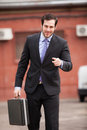 Handsome and expresive businessman walking on the street with a briefcase Stock Image