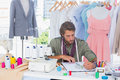 Handsome fashion designer drawing with pencils clothes Royalty Free Stock Images