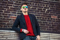 Handsome fashion man wearing casual jacket and sunglasses  standing near brick wall Royalty Free Stock Photo