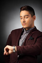 Handsome fashionable guy checking the time on his wrist watch Stock Photo