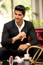 Handsome fashionable man Smoking Cigar in a Business Lounge Royalty Free Stock Photo
