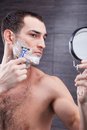 Handsome fit guy is caring of his appearance portrait attractive young man shaving stubble with a razor he standing and looking at Stock Photography