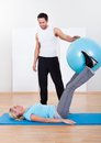 Handsome fit instructor helping a women with pilates exercises extending and stretching her leg as she sits on a gym ball Stock Photos