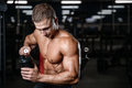 Handsome fitness model holding a shaker in the gym gain muscle Royalty Free Stock Photo
