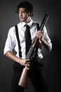Handsome gangster style model fashion dressed vintage with shotgun grey backdrop portrait Stock Photo