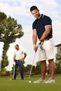 Handsome golfer holing young ready for on the green Royalty Free Stock Images