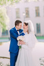 Handsome groom holds in hands beautiful bride's face close up outdoors Royalty Free Stock Photo