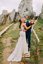 Handsome groom in stylish blue suit kissing his white dressed bride holding bouquet of roses on majestic mountain Royalty Free Stock Photo