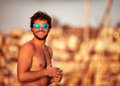 Handsome guy on the beach portrait of in mild yellow sunset light perfect athletic body summer vacation luxury sailboat Royalty Free Stock Photo