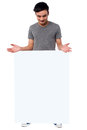 Handsome guy behind blank ad board smiling young with white poster Royalty Free Stock Photo