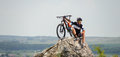 Handsome guy with bike on top of the mountain Royalty Free Stock Photo