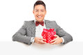 Handsome guy with bow tie holding a gift behind a panel Royalty Free Stock Photography