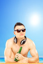 Handsome guy with headphones and sunglasses drinking beer cold on beach next to a sea Stock Photography