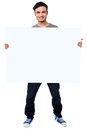 Handsome guy holding blank ad board smiling young white poster Stock Image