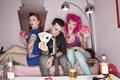 Handsome guy holding playing cards with tattooed women sitting besides Royalty Free Stock Photo
