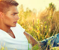 Handsome guy lying on the field young man enjoying nature Royalty Free Stock Photos