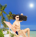 Handsome guy relaxing on a chair with radio on his shoulder on tropical beach next to sea and palm trees shot tilt and Royalty Free Stock Photography