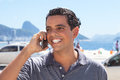 Handsome guy at rio de janeiro speaking at phone with sugarloaf mountain and ocean in the background Stock Image