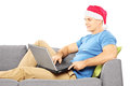 Handsome guy with santa hat seated on a sofa working on a laptop isolated against white background Stock Image
