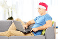 Handsome guy with santa hat on a sofa working on a laptop at hom seated home Stock Photography