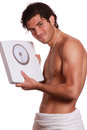 Handsome happy man and weighting machine Stock Photos