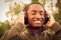Handsome hispanic black man wearing green sweater in outdoors park area, hands holding headphones covering ears and Royalty Free Stock Photo