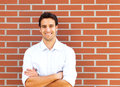 Handsome latin guy in front of a brick wall laughs an old Stock Photo
