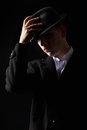 Handsome mafioso man touching hat in the dark Royalty Free Stock Photo