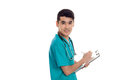 Handsome male doctor in uniform with stethoscope on his neck looking at the camera and make notes isolated on white Royalty Free Stock Photo
