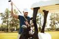 Handsome male golfer taking clubs from a bag in a golf cart Royalty Free Stock Photo