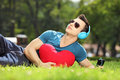 Handsome male lying on a grass with red heart listening music green Royalty Free Stock Photo
