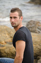 Handsome male model sitting on rock by the sea Royalty Free Stock Images