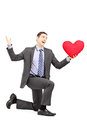 Handsome male in a suit kneeling with red heart isolated on white background Stock Photos