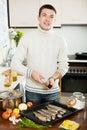 Handsome man adding seasonings in fish on baking sheet at home kitchen Royalty Free Stock Photos