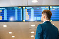 Handsome man in the airport checking his flight data rear view of businessman formalwear checking time and looking at flights Stock Photo