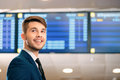 Handsome man in the airport just time for check low angle image of a businessman wearing suit smiling away while standing against Royalty Free Stock Photos