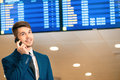 Handsome man in the airport timely flight low angle image of a businessman wearing suit talking over mobile phone while standing Royalty Free Stock Image