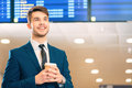 Handsome man in the airport travelling is his life businessman suit holding a cup of coffee and smiling while standing against Royalty Free Stock Photography