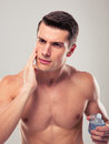 Handsome man applying facial lotion over gray background Stock Photography