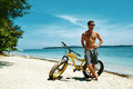 Handsome Man With Bike Sun Tanning On Beach. Summer Vacation. Royalty Free Stock Photo
