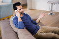 Handsome man calling on the couch Royalty Free Stock Photo