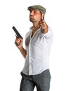 Handsome man in cap with a gun on white background Stock Photography