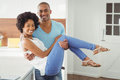 Handsome man carrying his girlfriend men in the kitchen Stock Images