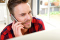 Handsome man on cellphone by window Royalty Free Stock Photo
