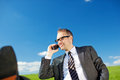 Handsome man chatting on his mobile low angle view of a business phone under a sunny blue sky Royalty Free Stock Images