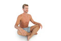 Handsome man doing yoga and sitting in lotus position on white background Stock Photo