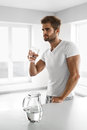 Handsome Man Drinking Glass Of Fresh Water Indoors In Morning Royalty Free Stock Photo